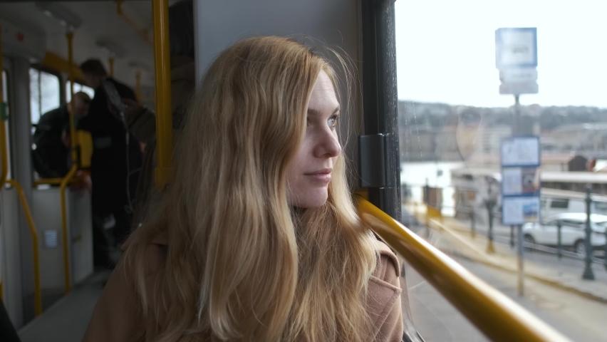 Portrait of a beautiful blonde woman in a tram by the window    Shutterstock HD Video #1063443064