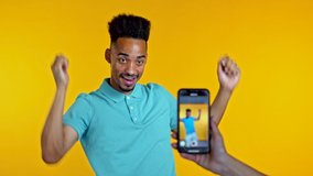 Smiling vlogger african man recording video of hisself dancing in front of smartphone camera on yellow background. Influencer makes funny social media clip