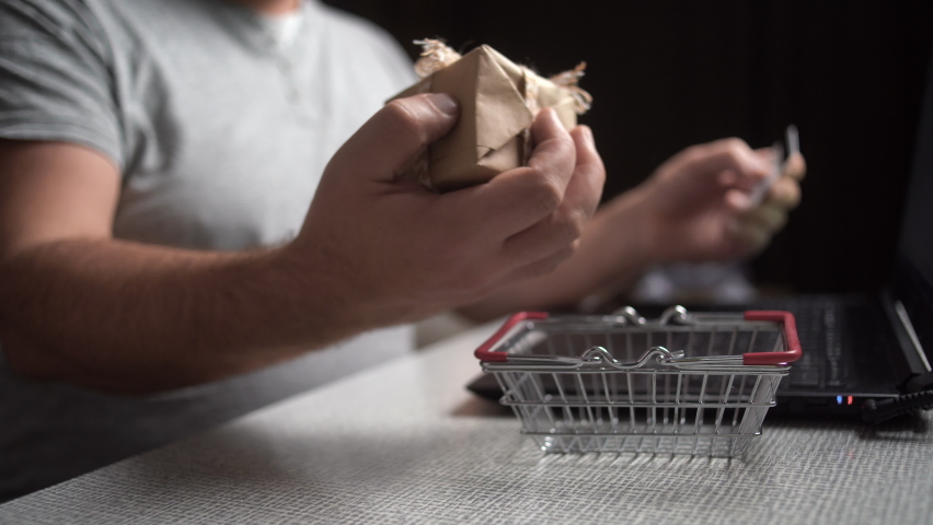 hands are typing numbers on the keyboard and a female hand puts a shopping basket with a box on the table. Online shopping gift concept Royalty-Free Stock Footage #1063457575