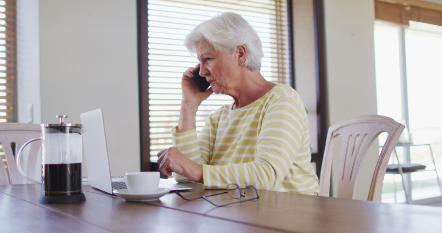 Senior caucasian woman with laptop talking on smartphone at home. retirement senior couple lifestyle living