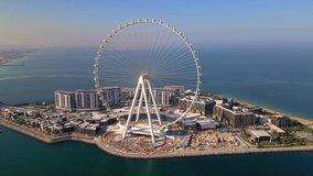 Bluewaters island and Ain Dubai ferris wheel on in Dubai, United Arab Emirates aerial footage. New leisure and residential area in Dubai marina area