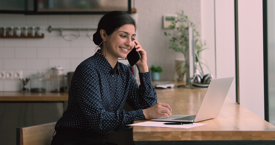 During quarantine all business solve remotely using modern wireless tech concept. Indian woman sit at bar counter in home kitchen hold smartphone talks to client distantly, provide help by phone call Royalty-Free Stock Footage #1063468012