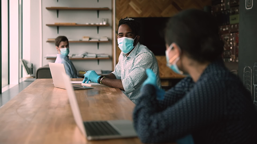 Multi ethnic staff sit at co working space with laptops, joking laughing during workday in modern office. Wear facial masks, gloves, keeping distance, personal safety due covid pandemic spread concept Royalty-Free Stock Footage #1063468036