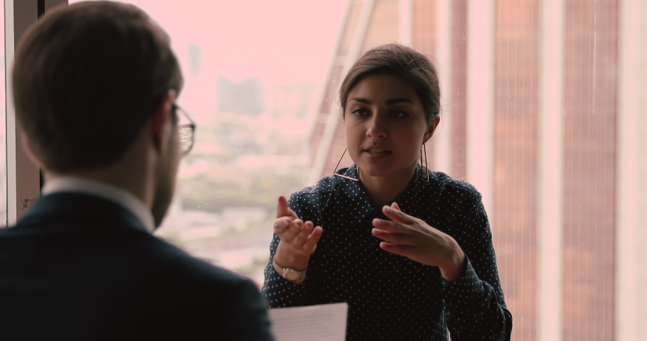 Confident vacancy candidature indian ethnicity female applicant answers question during job interview, hr manager rear view. Business meeting, parties negotiations process in modern office concept Royalty-Free Stock Footage #1063468069