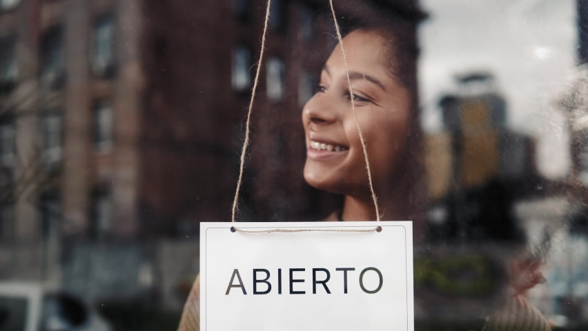 cafe or restaurants and business reopen after coronavirus quarantine is over. woman with face mask turning a sign on a door shop. small business after covid lockdown. On spanish business open sign. Royalty-Free Stock Footage #1063470055
