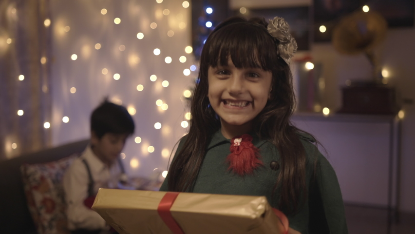 A well-dressed adorable young female kid is smiling while receiving the Christmas present in a decorated house. Happy and excited girl accepting the gift-wrapped box from parents  Royalty-Free Stock Footage #1063470406