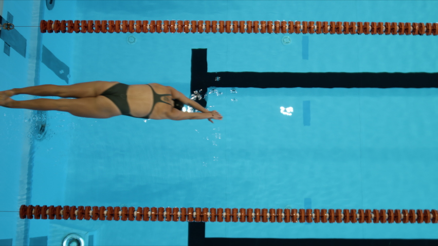 Slow motion shot of a woman jumps into indoor swimming pool to start training. View from above. Royalty-Free Stock Footage #1063476475