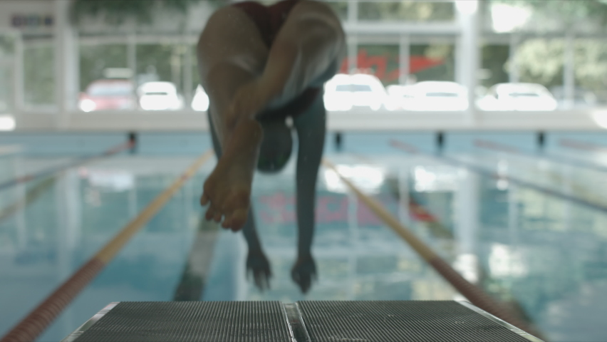 Swimmer on the starting blocks before she start training swimming. She jumps into the pool in slow motion. Royalty-Free Stock Footage #1063476553