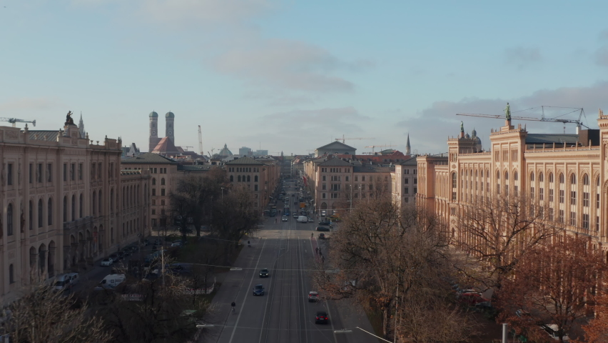 Main Road through Cityscape center of German City Munich with classic buildings and tram rails and car traffic, Scenic Aerial Dolly in