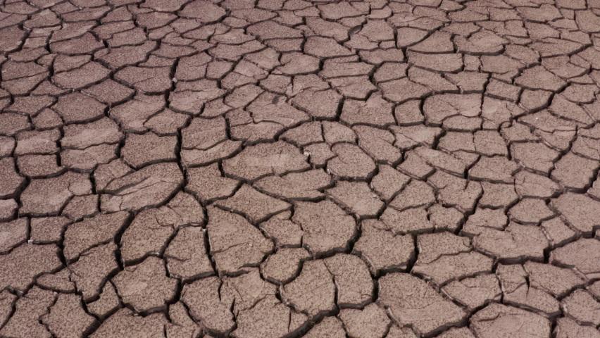 A view of a cracked surface of a parched lake. The concept of global warming, environmental pollution and post-apocalypse | Shutterstock HD Video #1063484713
