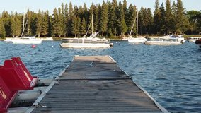 Clip of boats on beautiful blue lake taken asing down an old wooden dock. Lake is surrounded by green fir trees. Water is wavy. Summertime, outside.
