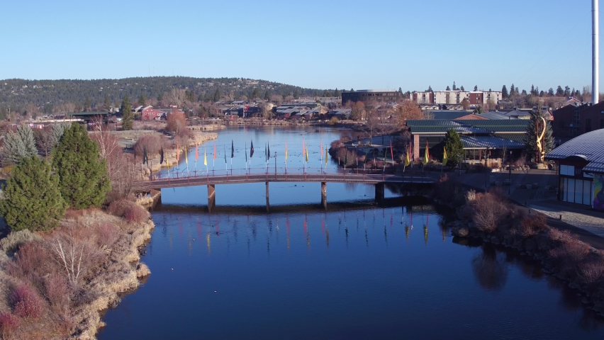 Flying over the Deschutes River in the Old Mill district in Bend Oregon, overflying the footbridge between Old Mill and the Les Schwab Ampitheater Royalty-Free Stock Footage #1063510303