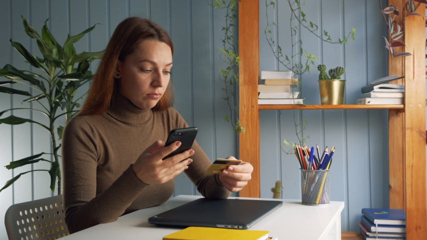 Woman holding plastic card and smart phone, buying on internet. Spend money use webshop Royalty-Free Stock Footage #1063520566