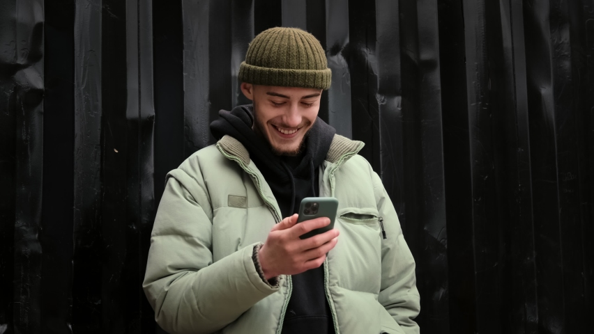Young student hipster man using touch mobile phone outdoor on the street. Surfing social media, checking news, playing mobile games, texting message. Royalty-Free Stock Footage #1063521901