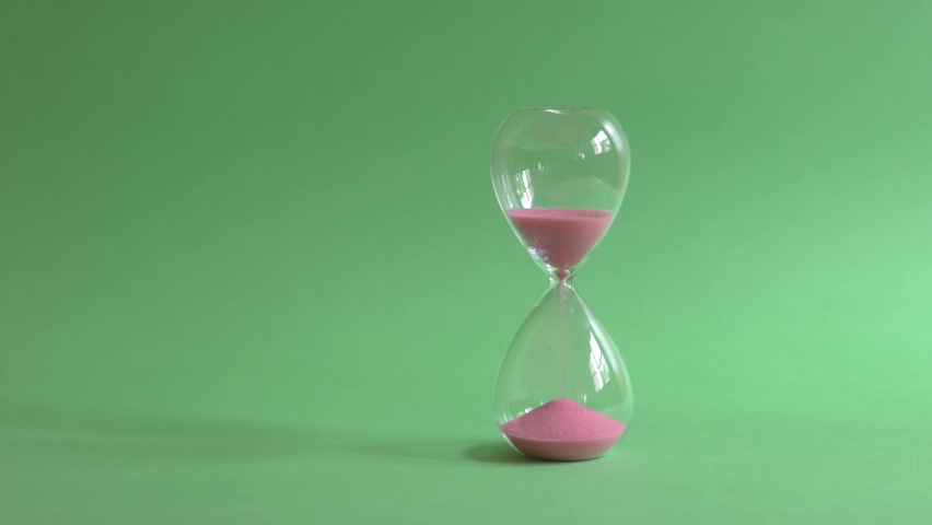 Hourglass sand timer on green background. Royalty-Free Stock Footage #1063554376