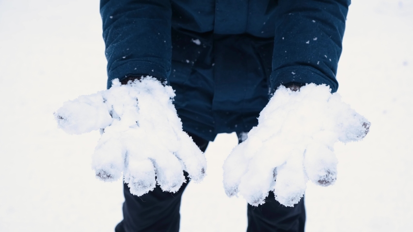 Close up man shakes off snow from his knitted gloves. Cold snowy winter in details. Royalty-Free Stock Footage #1063559779