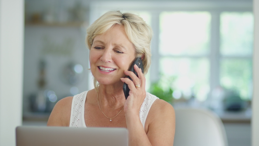 Close up of smiling retired senior woman on phone at home in kitchen using laptop - shot in slow motion