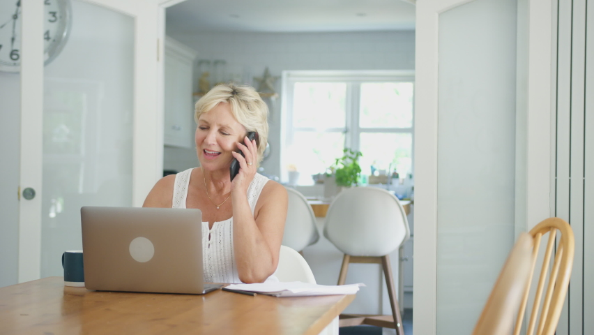 Smiling retired senior woman on phone at home in kitchen using laptop - shot in slow motion