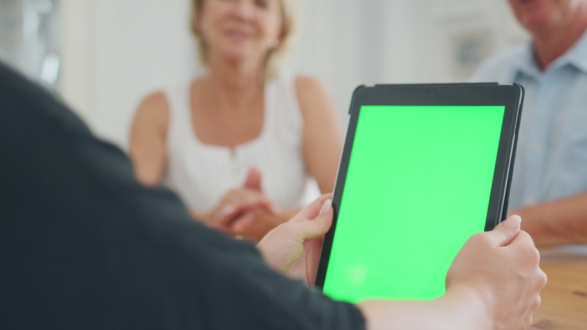 Close up on blank screen of digital tablet as retired couple meeting with financial advisor at home - shot in slow motion