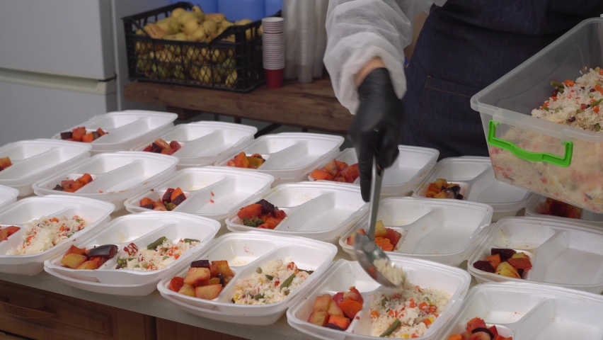 Volunteer packs free Christmas dinners in meal prep containers.  Holiday basket of groceries. Charities, churches, community soup kitchens, and restaurants serve a meal to a poor and needy Royalty-Free Stock Footage #1063561636