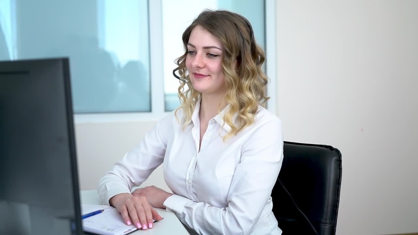 Beautiful young blonde girl manager in the company works in the office. manager communicates on the phone with a client sitting at a computer in the office. the director is negotiating via Skype in hi