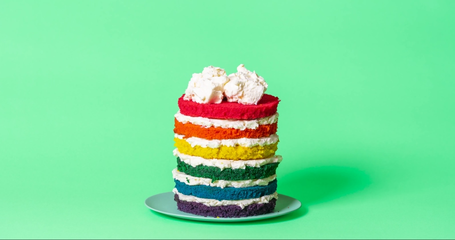 Stop motion animation with the assembling of a rainbow cake. Birthday cake making of step by step with buttercream and colored batters.  Royalty-Free Stock Footage #1063583944