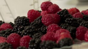 Black and red berries raspberries and blackberries fall on the plate. Fruits and berries are healthy food. Cook at home. Footage clip stock video