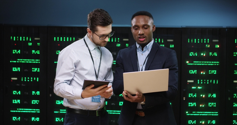 Caucasian and African American male analytics coworkers tapping on laptop and tablet and discussing data security issue working in data center. Man engineers speaking in data storage with server racks Royalty-Free Stock Footage #1063599058