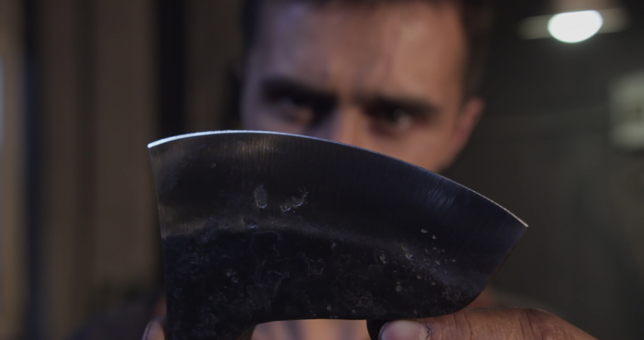 Close-up on the master's face, he raises the head of the ax in front of him, brings it to his eyes and checks the sharpening of the blade with his finger. High quality 4k footage Royalty-Free Stock Footage #1063615687