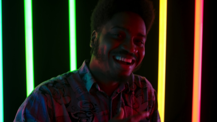 Portrait of a young stylish African American male smiling, dancing happily and sings. Slow motion. Close up.