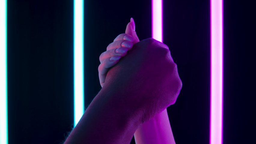 Anti racism symbol. Black and white hands clenched together in a fist in protest against the background of bright neon lights in a dark studio. Close up. Slow motion.
