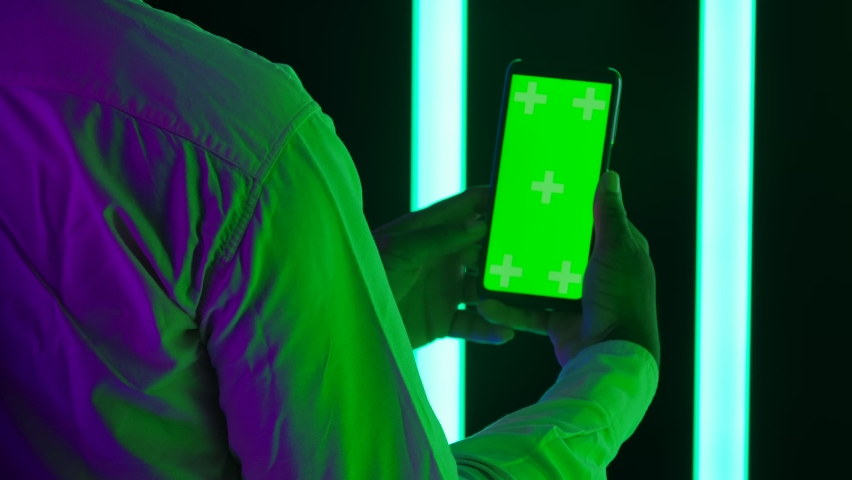 Back view of a young stylish male African American holds and touches green screen chroma key of his smartphone. Close up. Slow motion.