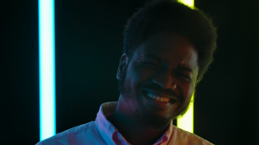 Portrait of a young stylish African American male smiling and enjoying the music. Close up. Slow motion.