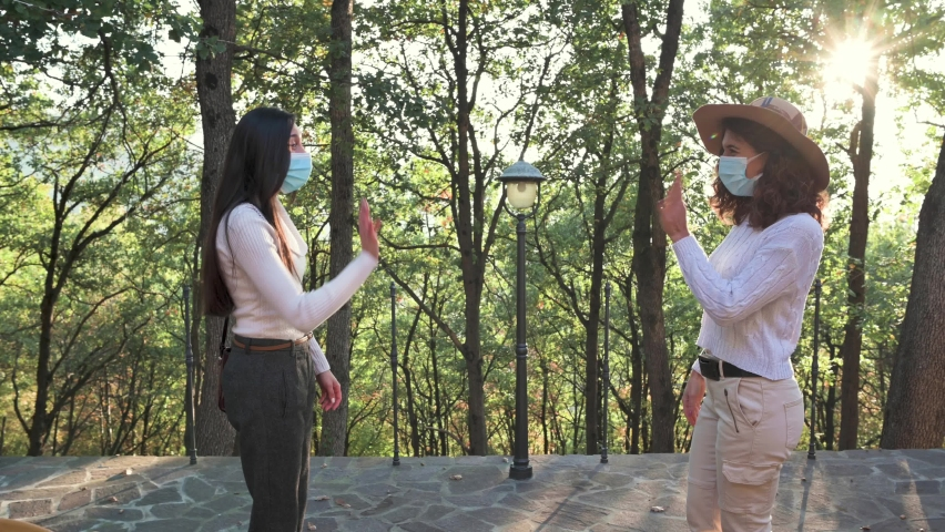 Two attractive young caucasian women with protective face mask meeting in a park. Alternative handshake with elbow. Pandemic concept, new normal, togetherness. Royalty-Free Stock Footage #1063628860