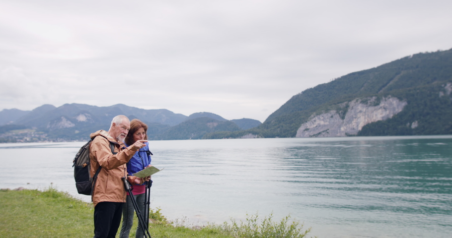Senior pensioner couple by lake with hiking in nature, using map. | Shutterstock HD Video #1063634053