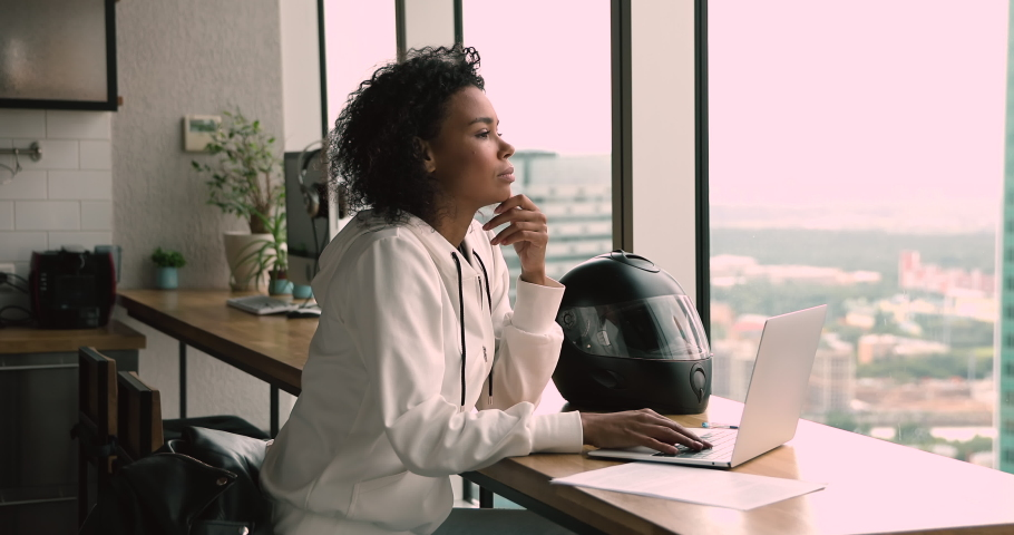 Pensive serious african 35s freelancer woman sit at table in modern office room alone working using laptop looking out the window thinking over business issue solution make telecommute job from home