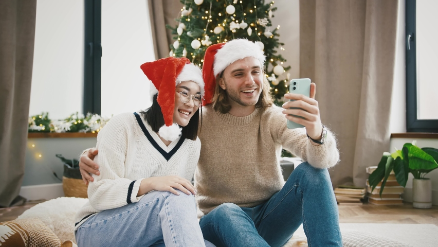 Young mixed race spouses in Santa hats smiling, hugging and saying hi to someone by online video call using mobile phone, sitting on floor near decorated Christmas tree. Happy New Year. Close up