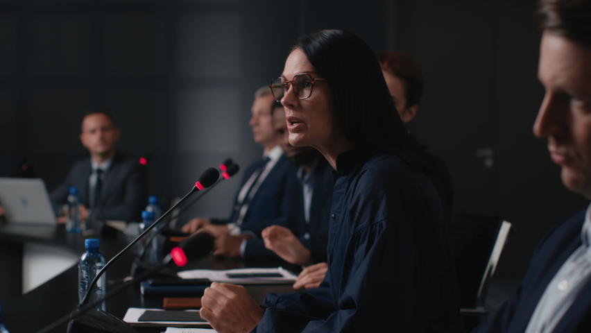 Political speaker talks at meeting room of modern business forum. Adult woman in suit discusses partnership at conference in convention hall. Expert diverse group working together at official event Royalty-Free Stock Footage #1063652929