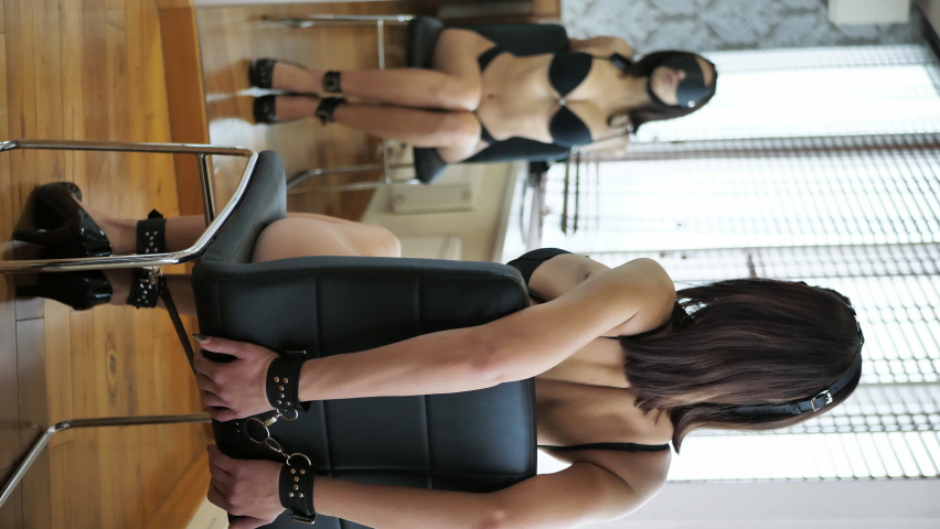 BDSM.Young woman in sexy leather underwear is chained to a chair before a session of sexual pleasures. Vertical video. The concept of secret desires