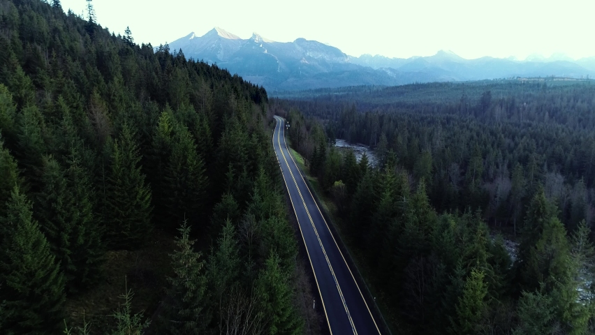 Aerial view of mountain twisted road. Cold autumn mountains and clean road through forest. Epic drone footage of highway in the wild mountain scenery. | Shutterstock HD Video #1063663588