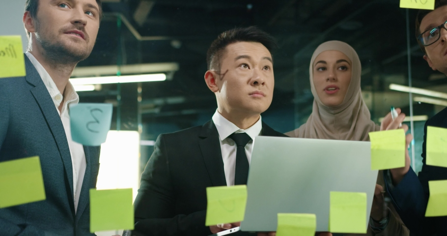 Close up of many mixed-races male and female professional coworkers working in modern office and writing on glass board discussing business startup project. Team work concept. Entrepreneurship Royalty-Free Stock Footage #1063665664