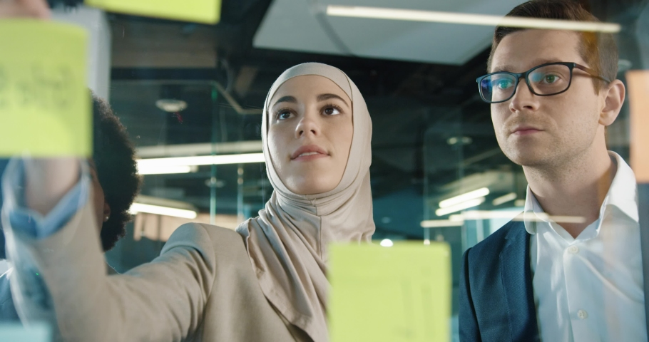Close up of mixed-races male and female professional working in modern office. Beautiful Arabian female writing on glass board in cabinet and speaking with colleagues. Business concept Royalty-Free Stock Footage #1063665673