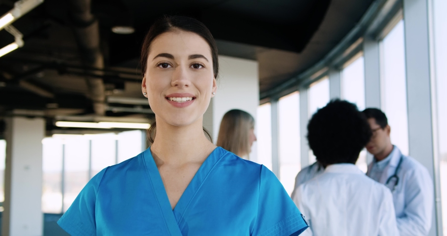 Close up portrait of cheerful young beautiful Caucasian female professional nurse healthcare assistant standing in modern hospital and smiling to camera in good mood. Doctors working on background Royalty-Free Stock Footage #1063665685