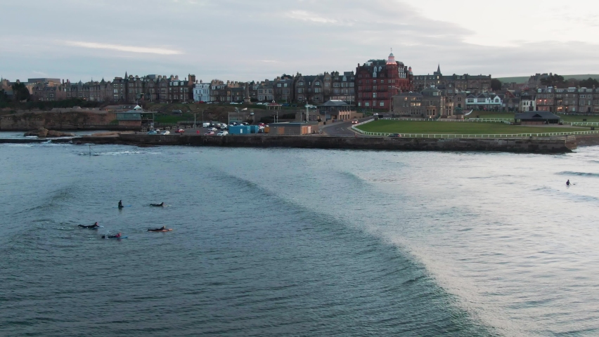 Aerial drone shot of Surfers in St Andrews in North Scotland on West Sands Royalty-Free Stock Footage #1063679401