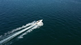 Large white boat fast movement on dark blue water to meet the sun at sunset, side view of the boat 4k video
