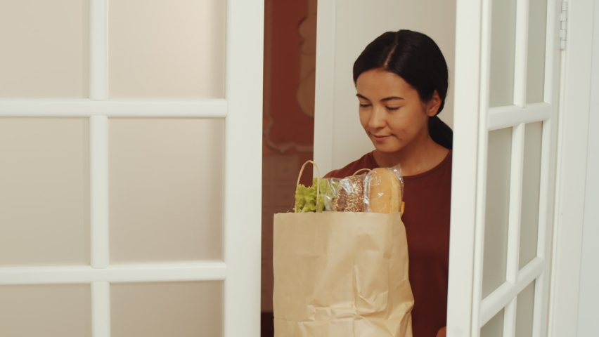 Young Asian female caregiver bringing bag of food to pensioner at home. Happy senior women giving her hugs and saying thanks Royalty-Free Stock Footage #1063684027