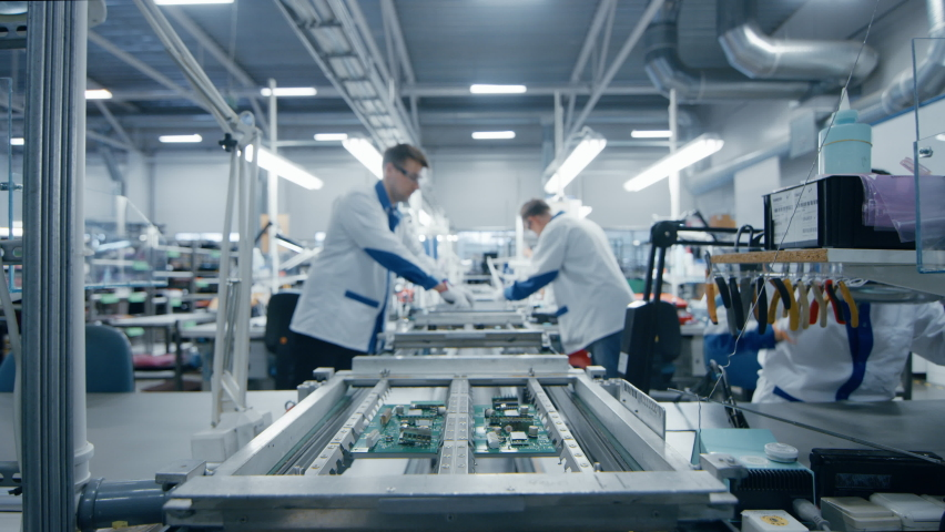 Modern High-Tech Electronics Factory Moving Manufacturing Conveyor: Professionals Doing Precision Work Assemble Circuit Boards, Processors, Microchips, Semiconductors. High-Quality Production Line Royalty-Free Stock Footage #1063689862