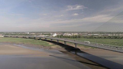Widnes , United Kingdom (UK) - 05 22 2020: Modern landmark Mersey Gateway transport bridge drone aerial view pan right across skyline
