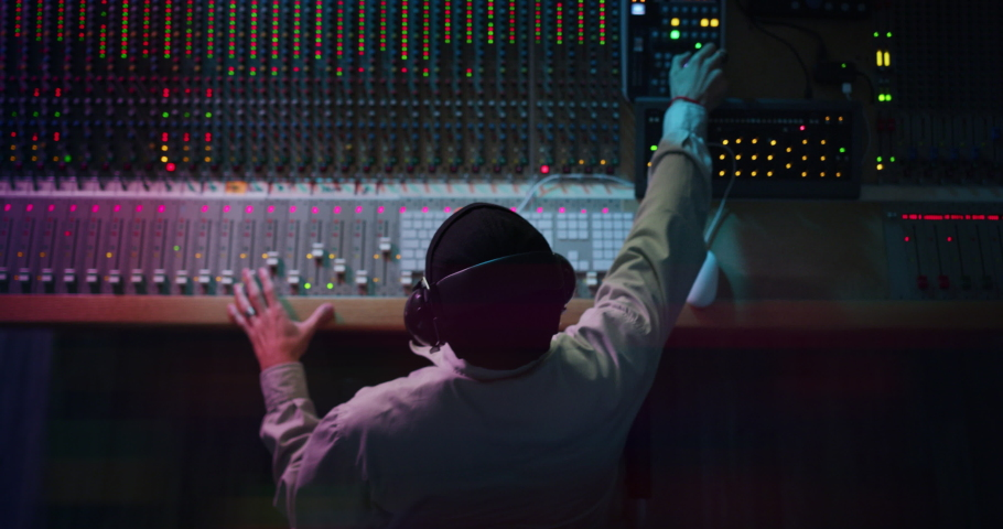 Cinematic top view of professional male sound producer with headphones is recording a new song with young singer in a music studio with colorful lights on a background.
