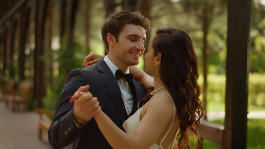 Closeup charming man and woman having first dance outdoors. Portrait of happy wedding couple dancing in garden. Cute bride and groom having fun on wedding ceremony. Royalty-Free Stock Footage #1063695709